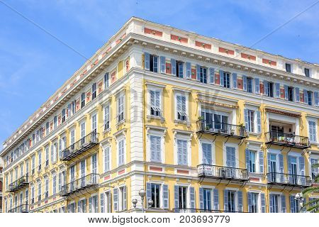Daylight view to yellow building of a hotel in Nice Cote d'Azur, France. Blue sky background.