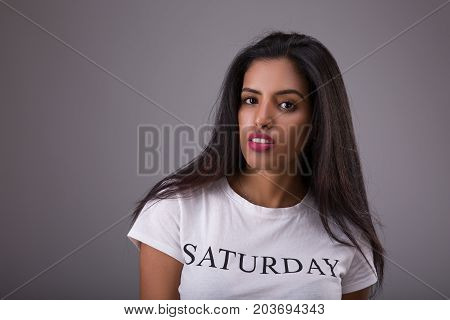 Portrait of Arabian or Indian woman dressed in white t-short with an inscription Saturday Studio shoot over gray background