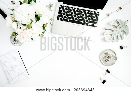 Flat lay home office desk. Female workspace with laptop white peony flowers bouquet accessories marble diary on white background. Top view feminine background.