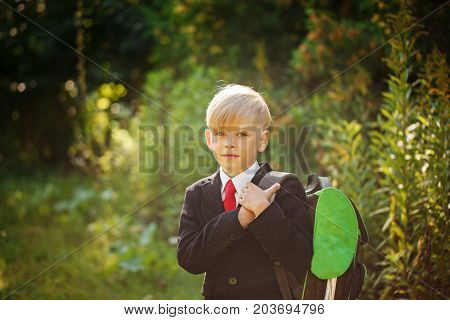 Cute boy going back to school. Boy in the suit. Child with backpack on first school day.