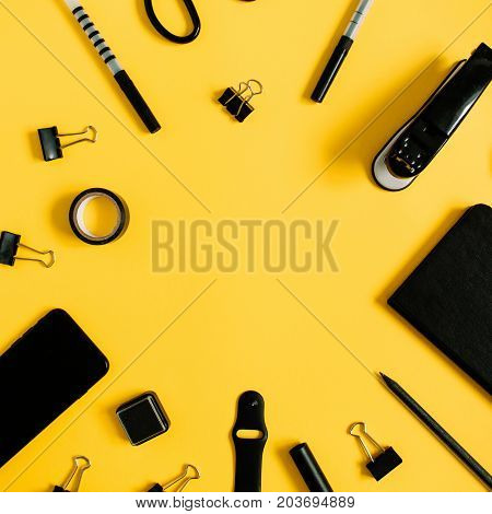 Flat lay home office desk. Workspace with male accessories: diary watch mobile phone on yellow background. Top view modern concept background.