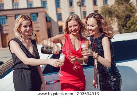 Beautiful women near the limousine have fun and drink champagne.
