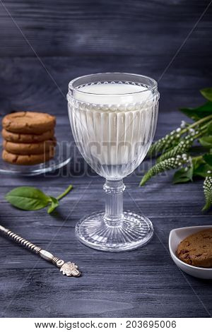 Gass of milk, chocolate cookies and flowers on a gray wooden background