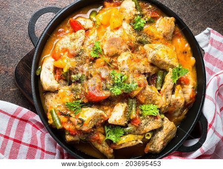 Stewed pork with vegetables in tomato sauce in a cast-iron pan. View from above.