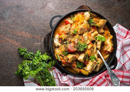 Stewed pork with vegetables in tomato sauce in a cast-iron pan. Top view on dark stone table with copy space.
