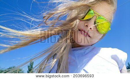 Girl with blond long hair and yellow sunglasses, the sea in the Sunny windy weather.