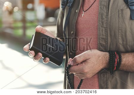 Close up male pensioner hand holding bible with christcross on it and beads