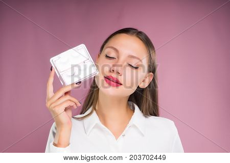 A beautiful girl with closed eyes is holding a box with false eyelashes in her hands. Isolated on a pink background