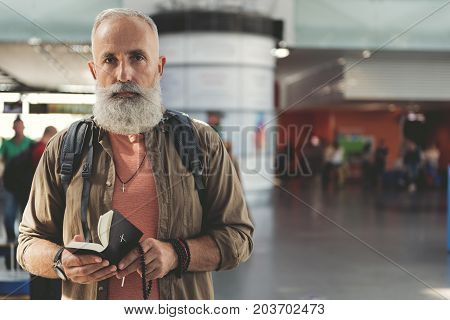Portrait of serious bearded old man reading holy book while standing in airport hall. Copy space