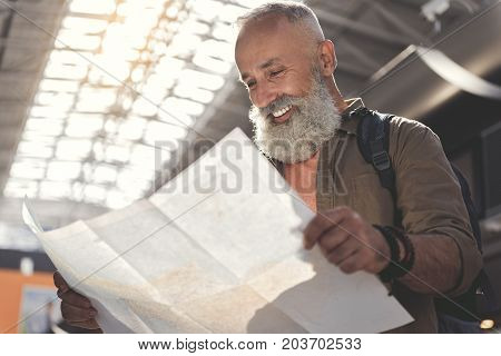 Low angle outgoing unshaven retire looking at map while keeping it in hand. He is wearing backpack