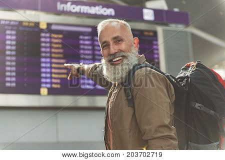Portrait of cheerful bearded retire man demonstrating on timetable in airport