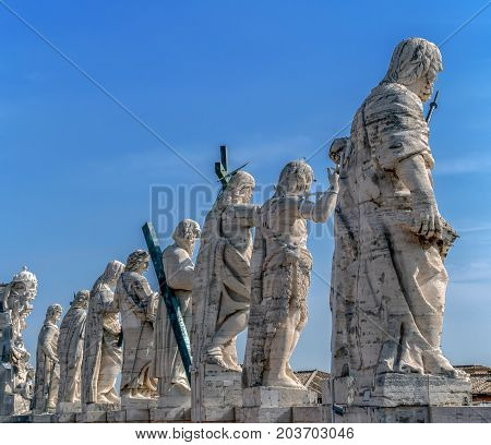 Back view of statues of the saints apostles located on the top of St Peter Basilica roof. Vatican City Rome Italy.