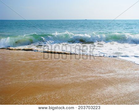 Waves break on the sandy beach, which leads to the appearance of a large amount of foam and spray.