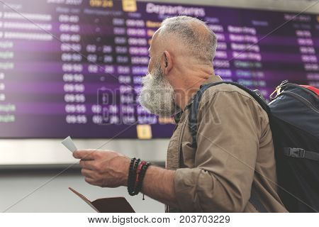 Unshaven old man looking at timetable while keeping card in arm in airport