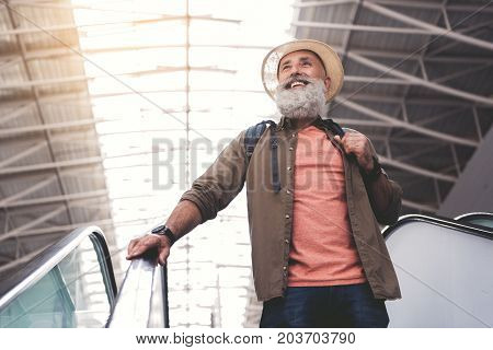Low angle portrait of unshaven beaming grandfather standing on escalator in airport
