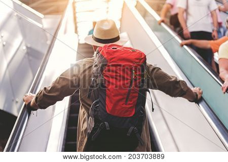 Low angle old man situating on moving staircase. He keeping big bag while turning back to camera