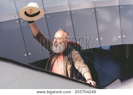 Beaming bearded pensioner waving hand with hat while standing on escalator in airport
