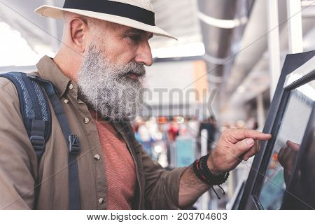 Side view serene bearded pensioner pushing on automatic teller. He looking at terminal