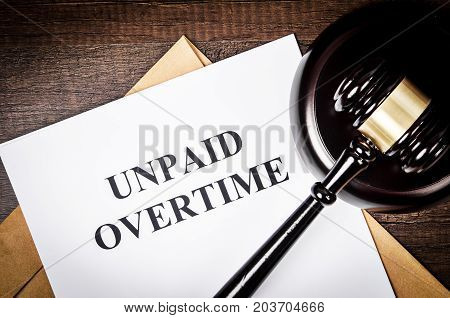 Unpaid Overtime title On Legal Documents with wooden gavel.