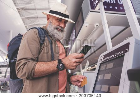 Low angle smiling unshaven pensioner typing in phone while standing near cash machine in airport
