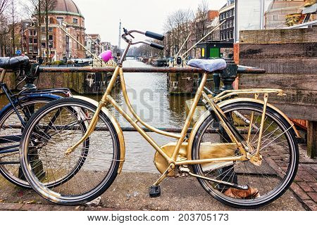 Gold bike leaning against railing over a canal in Amsterdam