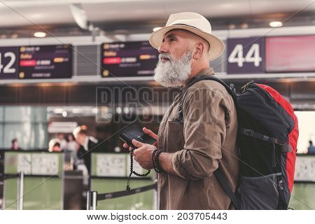 Side view serene bearded grandfather keeping holy book and accessories in arm while standing in airport