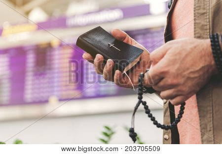 Close up male hands holding bible with christ on envelope and beads in hand. Airport timetable on background