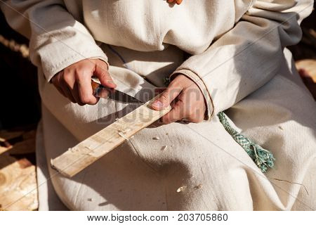 Hands Holding Sharp Knife And Wooden Plank