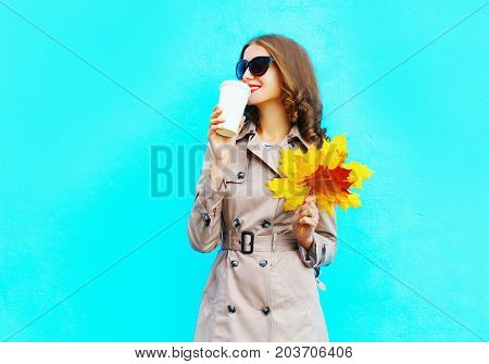 Fashion Woman Drinks Coffee From Cup Holds Autumn Yellow Maple Leaves On A Blue Background