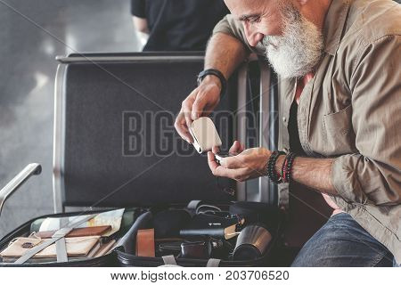 Side view outgoing bearded old man watching at course detector while locating near big suitcase with objects for long travel. Trip concept