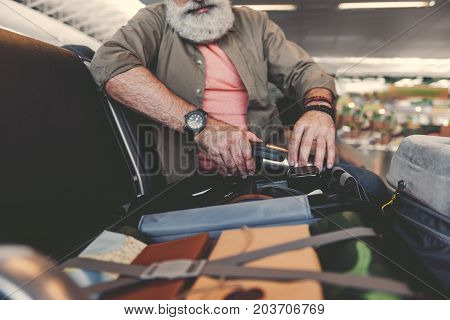 Serene bearded grandfather checking bag with various things for journey while sitting in concourse in airport. low angle. Journey concept