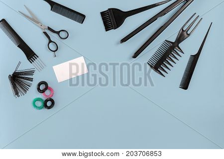 Hairdresser tools on blue background with copy space, top view, flat lay. Comb, scissors, thinning scissors, hair clip. Still life.