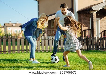 Upbeat weekend. Pretty little girl playing soccer with her beloved parents on the green lawn of their backyard, being about to kick the ball poster