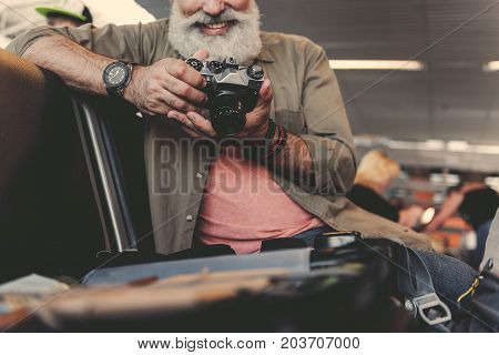 Close up bearded old man arm looking at images on camera. He situating on comfortable chair in waiting room. Low angle. Trip concept