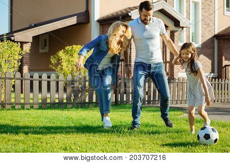 Fun time. Beautiful young family having fun, playing football in the yard of their house and having fun