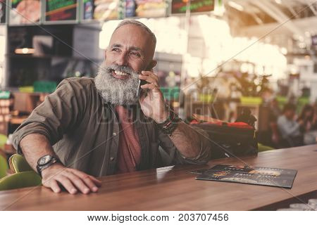 Portrait of cheerful unshaven pensioner telling by mobile while sitting at desk in confectionary shop