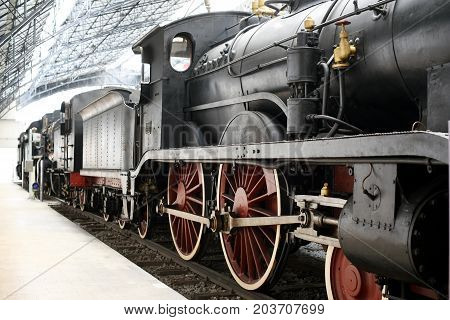 Old vintage train with steam locomotive standing at railway station