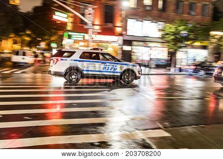 NEW YORK USA - AUGUST 29 2017: Police car rushing on the street panning view with blurred background. NYPD car with emergency lights