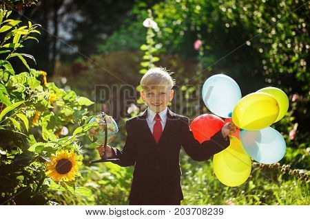 Cute boy going back to school. Boy in the suit. Child with globe and colorful balloons on first school day