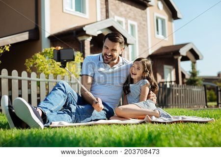 Fatherly love. Pleasant young man sitting on the rug next to his little daughter, hugging her and taking a selfie with a selfie stick while laughing
