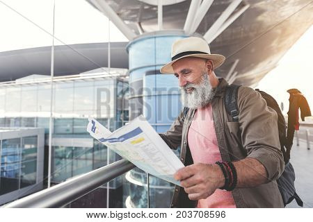Glad mature tourist is standing near building and looking at map with smile. He wearing hat. Copy spce on left side