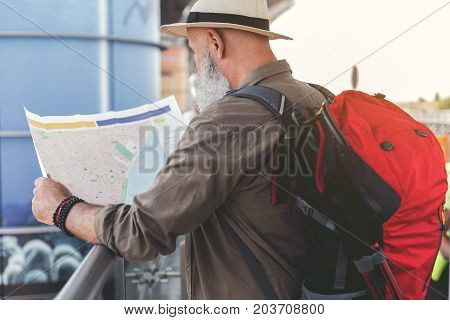 Mature man is standing near handrail and holding unfolded map. He carrying big red backpack