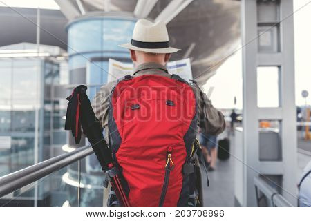 Mature tourist is holding red backpack and moving forward. He reading unfolded map. Focus on baggage. Copy space on right side
