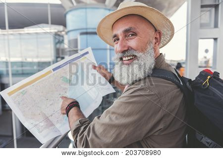 Cheerful mature bearded tourist is pointing on certain place at unfolded map. He looking ahead with smile. Portrait. Copy space on left side