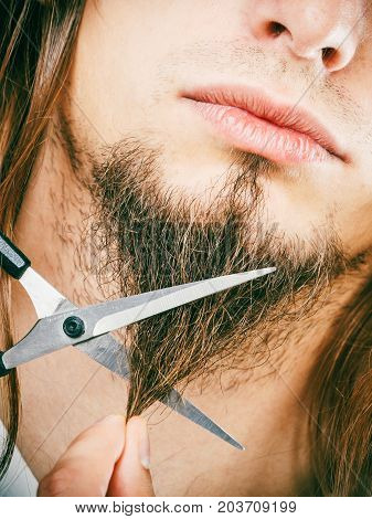 Cut and shave concept. Young man with long beard holding scissors. Part face boy cutting hair on chin.