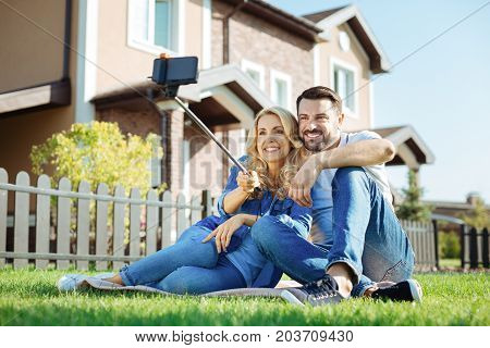 Seizing the moment. Beautiful young couple sitting on the rug near their recently bought house and taking a selfie together
