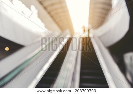 Modern escalator in tremendous public building. Defocused photo of airport. Copy space. Low angle