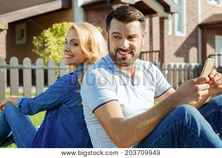 Always together. Lovable middle-aged couple sitting back-to-back on the grass, turning their heads to each other and smiling while the man holding a phone