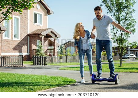 First experience. Pleasant smiling woman holding a hand of her husband riding a self-balancing scooter for the first time, providing support to him