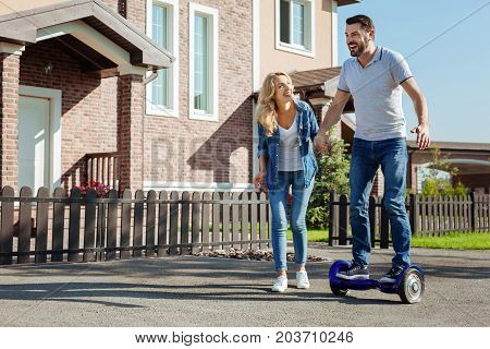 Exciting experience. Charming young man riding a self-balancing scooter for the first time and holding his wifes hand, seeking support